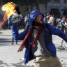 An anti-government protester throws a firebomb at police amid a march by students and union members in Santiago, Chile on Monday.