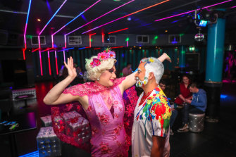 Drag queen Charisma Belle and Kevin Kaila with patrons inside ARQ.
