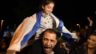 Noya Dahan, 8, rides on the shoulders of her father, Israel Dahan, at a candlelight vigil.