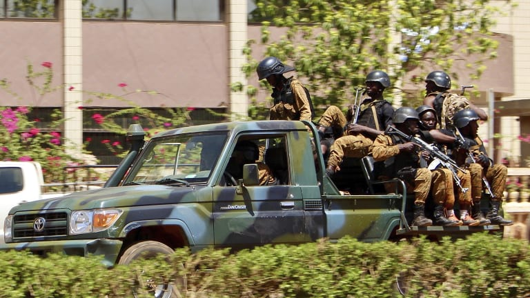 Troops ride in a vehicle near the French Embassy in Burkina Faso after gunfire and explosions rocked the capital.