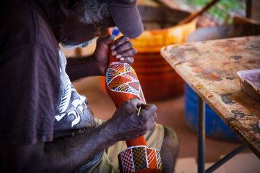 A Tiwi Island artist painting a carved wooden bird.
