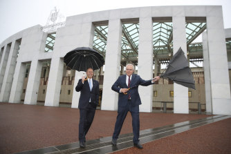 Treasurer Josh Frydenberg and Prime Minister Scott Morrison arrive for post-budget day interviews on a windy, rainy morning.