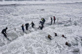 Swimmers hold the fence chains at North Narrabeen Rockpool as huge waves hammer the Sydney coast.