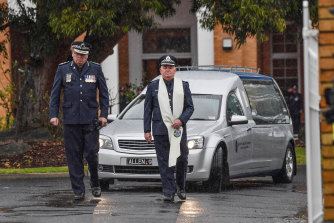 Victoria Policechief commissioner Graham Ashton (left) led the funeral procession after Glen Humphris was farewelled by his partner and family on Friday.
