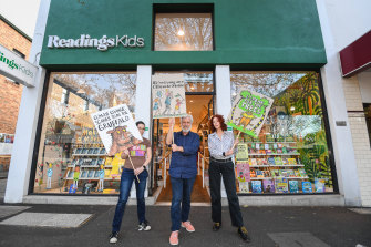 Readings Kids will be closed for the climate rally. L-R Dani Solomon, Mark Rubbo and Angela Crocombe. Placards by Artist Pilgrim Hodgson.