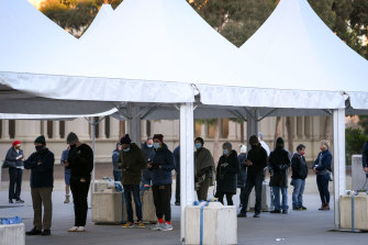 People queue to receive the COVID-19 vaccine at the Royal Exhibition Building in Carlton on Monday.