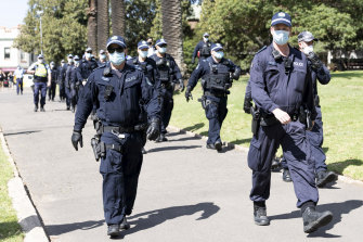 The riot squad walks through Victoria Park next to the Sydney University campus.