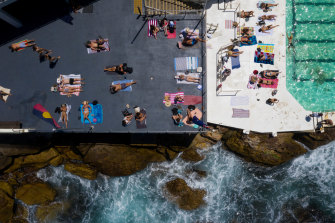 Swimmers sunbake at Icebergs in Bondi.