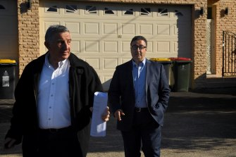 Shaoquett Moselmane, right, with his lawyer as he leaves his home on Lennox Street in Rockdale during a raid by federal agents.