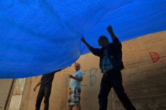 Civilians in the border town of Darbasiyah erect tarpaulins in the streets to hide their movements.