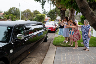 Parents of the Our Lady of Mercy College Parramatta group wave goodbye to their daughters as they depart for the formal in a limousine.