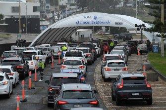 Cars queue at the Bondi Beach drive-through COVID-19 testing clinic.