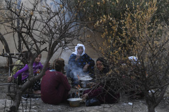 A family who fled Ras al-Ain sit round a fire in Tal Tamr.