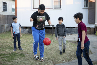 'It's hard to balance': Ghanim al-Shnen plays football with his sons, who will soon return to their home in Finland.