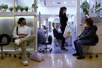 Pauline Pinete (left) waits to enter a nail salon in Westfield Bondi Junction shopping centre on the first day of relaxed COVID-19 restrictions