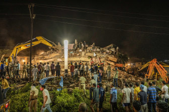 Rescue workers look for survivors after the residential building collapsed in Mahad.