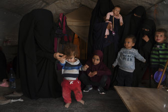 Australian women and children gather in a tent in the al-Hawl camp where they watch Omeid, who suffers with spinal deformities and malnutrition, attempt to walk.