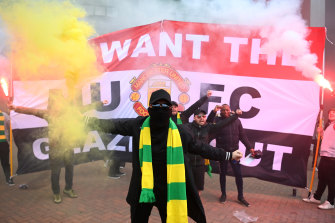 A fans wearing Manchester United's green-and-gold formation colours outside Old Trafford on Sunday.