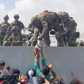 A baby is lifted across a wall at Kabul Airport in Afghanistan by US soldiers.