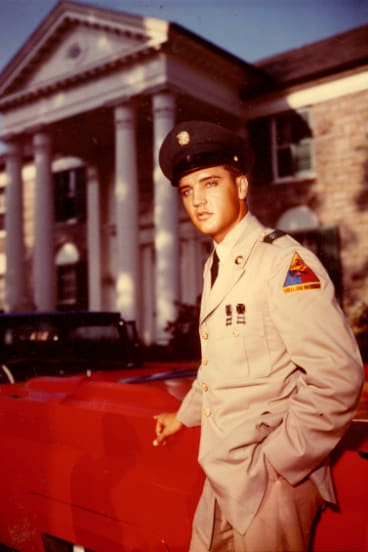 Elvis Presley in an army uniform outside Graceland.