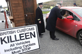 Men dressed as British customs officers stop traffic during an Irish anti-Brexit spoof on the Old Dublin Road at Carrickarnon, near the border with Northern Ireland.