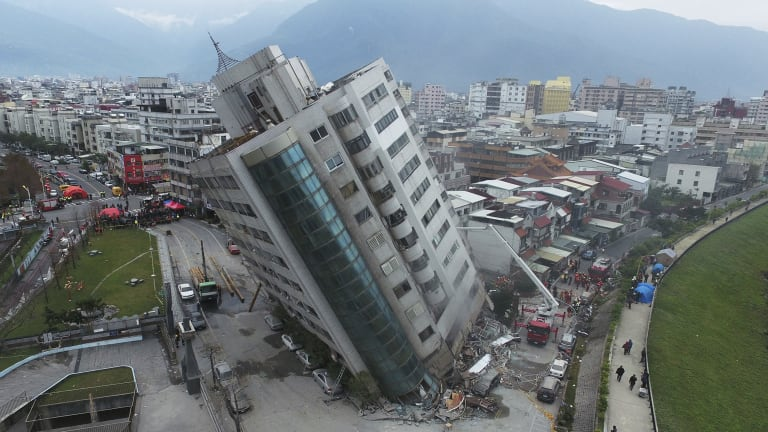 A building teetered on Wednesday after its first floor collapsed in an earthquake in Hualien, in Taiwan's east.