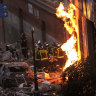 Fire-fighters carry a dead body next to a damaged building at Toledo Street following a powerful explosion in downtown Madrid, Spain.