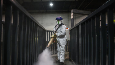 A volunteer  fumigates a bus station in Beijing. Experts are now looking to the economic ramifications of the coronavirus.