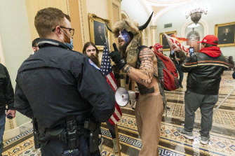 Jacob Chansley, pictured in face paint and  wearing a fur hat with horns during the riot, has been charged by police.