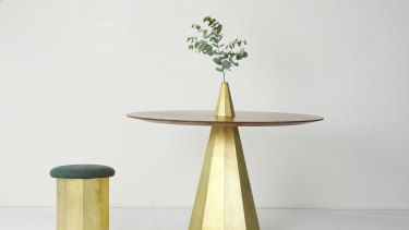 The dining table has elements of folded solid brass in a sculptural form, with a beautifully shaped top in oak or walnut timber.