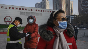 A Chinese woman wears a protective mask as she has her temperature checked entering a park in Beijing.