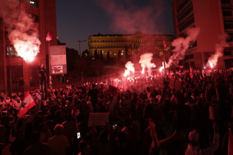 Anti-government protesters light flares and shout slogans in Lebanon's capital, Beirut, this week.
