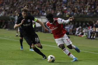 Arsenal's Bukayo Saka (right) runs the ball as Frankfurt's David Abrahim hovers.