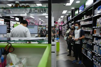 Cabramatta pharmacist Quinn On, at work on the left, worries he will waste his Moderna shots.