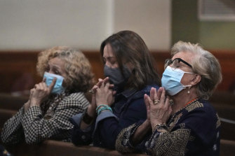 Women pray, late on Saturday, at a vigil for the victims and families of the Champlain Towers collapsed building in Surfside, Florida, at the nearby St. Joseph Catholic Church in Miami Beach.