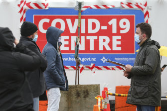 A staff member talks to people waiting to be tested for COVID-19 in Wellinton.