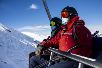 Skiers wearing face masks ride a chairlift on the opening day of the Verbier ski area in the Swiss Alps.