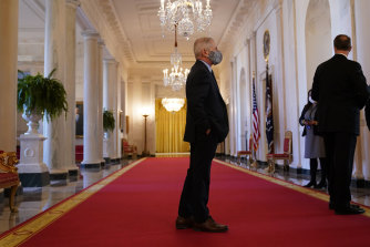 Dr Anthony Fauci stands in a hallway before an event with President Joe Biden on the coronavirus at the White House