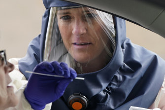 A nurse takes a swab from a patient at a drive-through coronavirus testing site in Salt Lake City.