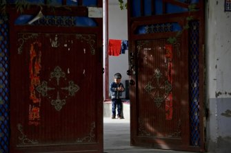 A Uighur child plays alone in the courtyard of a home at the Unity New Village in Hotan, in China's Xinjiang region. There have been reports of forced sterilisations of the Uighurs by the government.