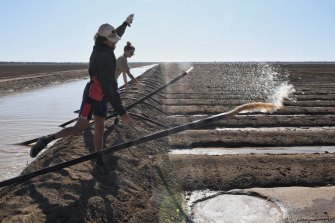 "Joseph Williams (left) and Angel Gale ""throw the pipes"" to siphon water into irrigation channels."