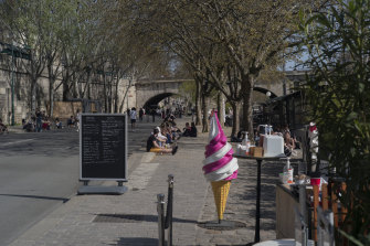 People enjoy warm weather along the Seine river banks in Paris this week before the introduction of tougher measures.