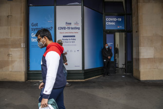 Masked pedestrians walk past a coronavirus testing clinic outside Central Station on Friday.