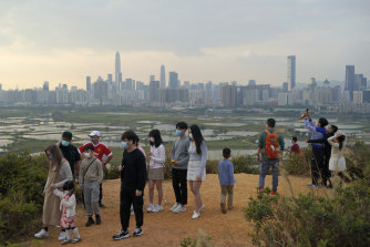Hong Kong citizens on the border, with China's Shenzhen in the background.