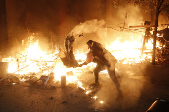A protester attempts to extinguish the flames after his tent was set on fire.