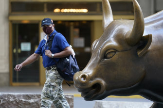 A man wearing a mask passes the charging bull statue in Manhattan.