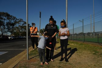 Latisha Carr-McEwan with her children waiting in a queue for a COVID-19 test at the Dubbo West walk-in clinic.