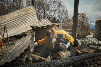 Volunteer firefighter Anika Craney searches through the remains of her home near Cobargo.