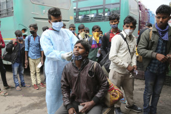 A health worker tests a man for COVID-19 at a bus station in Jammu, India, last month.