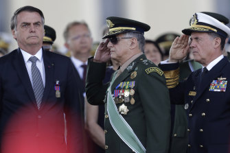 Brazil's President Jair Bolsonaro, left, receives military honours in 2019.